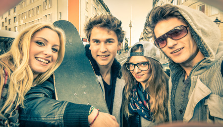 Young hipster best friends taking a selfie in urban city context - Concept of friendship and fun with new trends and technology - Urban alternative everyday life in Berlin european capital