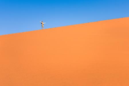Adventurous man lonely traveler hiking on sand dune at Deadvlei near Sossusvlei - Namibian world famous desert - Adventure trip to african nature wonder shooting travel photography photo