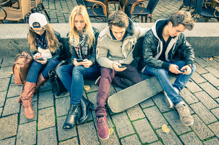 Group of young hipster friends playing with smartphone with mutual disinterest towards each other - Modern situation of technology interaction in alienated lifestyle - Internet wifi connection Stockfoto