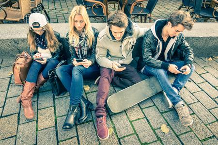 jovenes estudiantes: Grupo de amigos inconformista j�venes jugando con el tel�fono inteligente con desinter�s mutuo el uno hacia el otro - situaci�n moderna de la interacci�n de tecnolog�a en el estilo de vida alienado - conexi�n a Internet WiFi