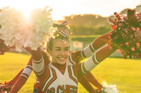 cheerleading squad: Portrait of a cheerleeder in action - Team sport and high school activities Stock Photo