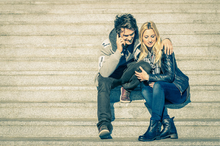 Beautiful hipster couple in love having a smartphone call - Modern concept of connection in a relationship together with mobile phone technology - City stairs urban lifestyle and everyday life rapport photo