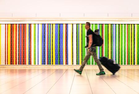 男はスーツケースと国際空港で歩くとバックパックのチェックイン後に搭乗の飛行機のため急いで - 世界中を旅代替ライフ スタイルのコンセプト -