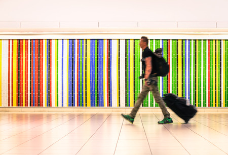 go inside: Man walking at international airport with suitcase and backpack - Concept of alternative lifestyle traveling around the world - Young hipster traveler in hurry for airplane boarding after check in Stock Photo