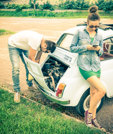 Couple in a moment of troubles during a vintage classic car trip - Concept of modern relationship and interaction with new technologies - Problem solving and lifestyle photo