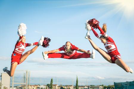 porrista: Equipo de animadoras de realizar un salto con el entrenador masculino
