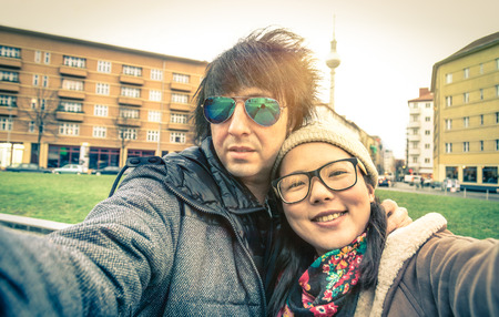 multi race: Hipster couple of tourists taking a selfie in Berlin City - Multiracial concept of friendship and fun with new trends and technology - Asian girl with alternative young fashion handsome guy Stock Photo