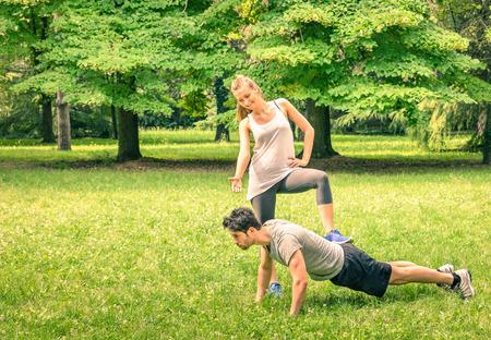 Vriendin bespotten haar vriend tijdens de training in het park - Jonge man en vrouw in het voorjaar training en sport activiteit - Mannelijke en vrouwelijke gelukkige paar fitness modellen te oefenen na het lopen