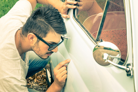 Young handsome man with sunglasses inspecting a vintage car body at second hand trade - Passion and transportation lifestyle of a retro classic vehicles collector