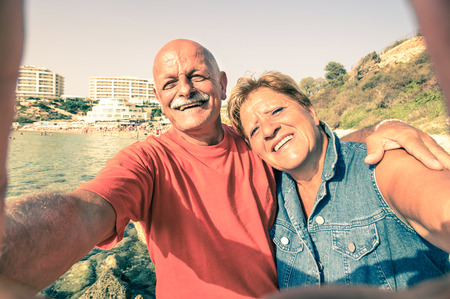 Senior happy couple taking a selfie at Blue Grotto resort in Malta south coast - Adventure travel to mediterranean islands - Concept of active elderly and fun around the world with new technologies