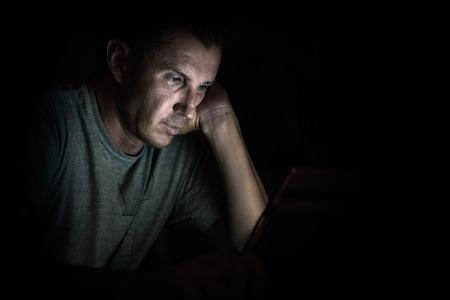 얼굴에 화면에서 빛의 반사와 노트북 컴퓨터에서 젊은 잘 생긴 남자 - 소외의 개념으로 인해 컴퓨터 장치 및 인터넷 중독에 소요되는 작업 시간 초과에