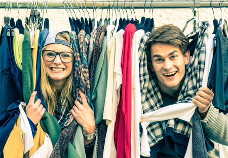 Young hipster couple in love at the weekly cloth market - Best friends sharing free time having fun and shopping in the old town - Lovers enjoying everyday life moments on a vintage filtered look photo