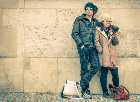 Multiracial couple in love on a phase of mutual disinterest - Modern concept of connection in a relationship together with mobile phone technology - City urban lifestyle and everyday life rapport 版權商用圖片