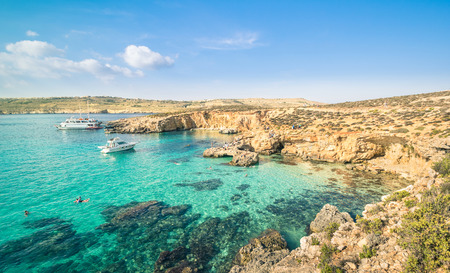 The world famous Blue Lagoon in Comino island - Mediterranean nature wonder in the beautiful Malta - Unrecognizable international tourist people and snorkeling divers - Exclusive travel destinations