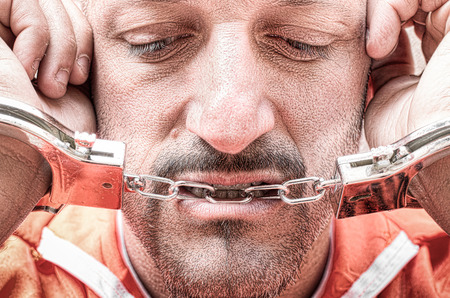 Sad depressed detained man with handcuffs in prison - Handcuffed inmate prisoner in jail with orange clothes - Crispy desaturated dramatic filtered look - Dead man walking concept and death penalty Stock Photo