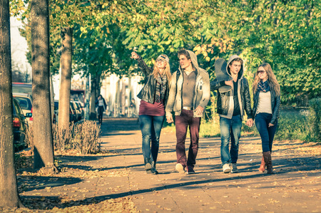 smiling teenagers: Group of happy best friends with alternative fashion look walking at the park - Hipster tourists having fun outdoors in sunny winter day - University students during a break hanging out together Stock Photo