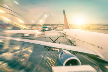準備離陸 - 日没 - 代替ライフ スタイルと世界恒久的な旅行の概念の間に搭乗機の現代国際空港ターミナルのゲートで飛行機