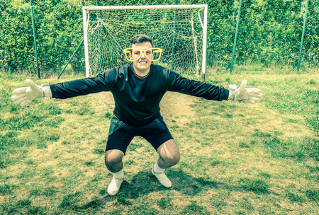 blindness: Funny goalkeeper at playground with stupid big empty glasses - Joke concept of blindness with playful attitude approach to sport competition