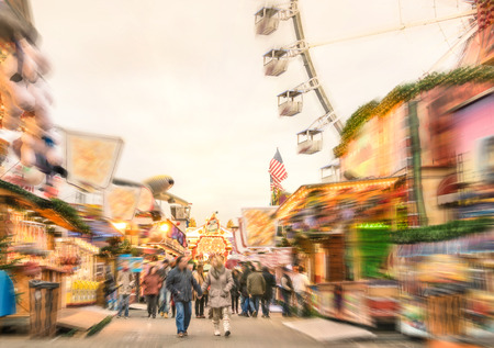 Crowd of people walking at luna park on a radial zoom defocusing - Multicolored fun stands at german Christmas market - Ferris wheel and colorful wooden houses at Berlin amusement area in winter time photo