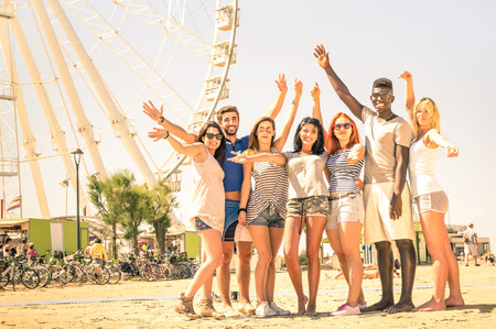 amusement: Group of multiracial happy friends cheering at ferris wheel - International concept of happiness and multi ethnic friendship all together against racism for peace and fun - Warm nostalgic filter Stock Photo