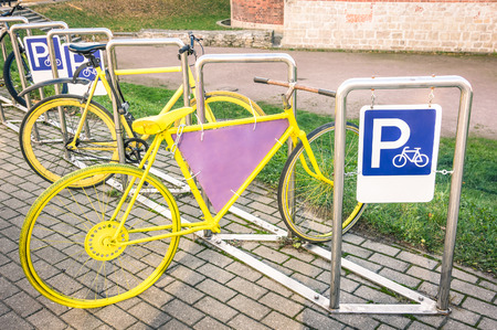 a two wheeled vehicle: Yellow vintage bicycle in metal rack in the old town of Riga Stock Photo