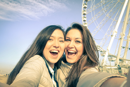 Young women girlfriends taking a selfie at luna park with ferris wheel - Concept of friendship and fun with new trends and technology - Best female friends catching the moment with modern smartphone photo