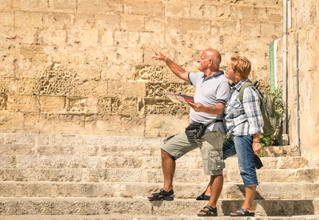 Happy senior couple exploring old town of la Valletta with city map - Concept of active elderly and travel lifestyle without age limitation - Trip to european mediterranean wonders