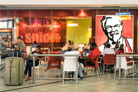 JOHANNESBURG, SOUTH AFRICA - NOVEMBER 28, 2014: melting pot people at KFC restaurant in Tambo International Airport. Kentucky Fried Chicken is a world famous fast food restaurant chain