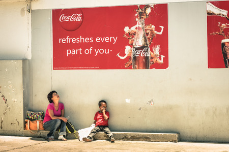 WINDHOEK, NAMIBIA - NOVEMBER 27, 2014: namibian mother and son sitting on floor under a Coca Cola poster. The country has a population of 2.1 million people and a multi-party parliamentary democracy