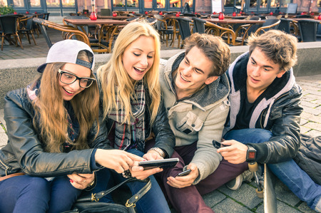 teenage girl happy: Group of young hipster friends having fun together with smartphone - Modern situation of technology interaction in everyday lifestyle - Internet wifi connection spots outdoors
