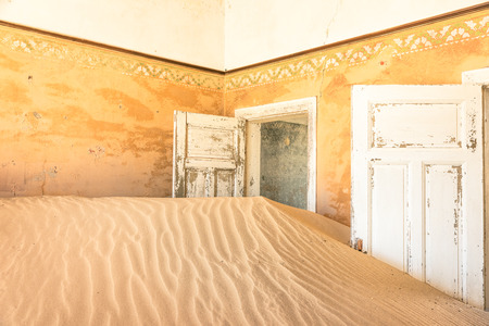 luderitz: Abandoned house full of sand from the desert in the ghost town of Kolmanskop - Sightseeing around Luderitz in Namibia - African wonders and mysteries Stock Photo