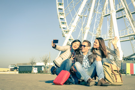 group picture: Young hipster people taking a selfie at luna park with ferris wheel - Concept of friendship and fun with new trends and technology - Best friends catching the moment with modern smartphone Stock Photo