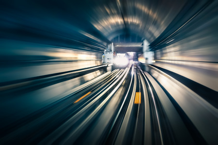 tunel: Túnel del subterráneo con pistas de luz borrosa con que llega el tren en la dirección opuesta - Concepto de transporte subterráneo de metro moderna y la velocidad de conexión