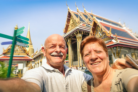 travel destination: Senior happy couple taking a selfie at Grand Palace temples in Bangkok - Thailand adventure travel to asian destinations - Concept of active elderly and fun around the world with new technologies