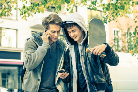 Young hipster brothers having fun with smartphone - Best friends sharing free time with new trends technology - Guys enjoying everyday life moments texting connected with modern smart phone device Stock Photo