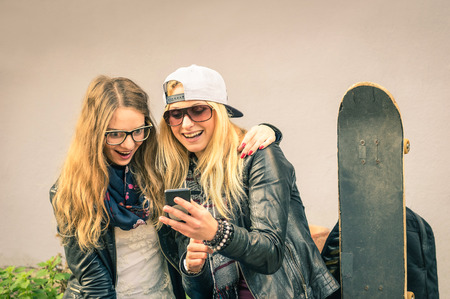 Best friends enjoying time together outdoors with smartphone - Concept of new trends and technology with hipster girlfriends having fun in urban city area - Alternative four seasons fashion clothes Stok Fotoğraf