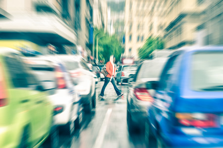 zoom in: Person crossing the road during rush hour in Cape Town - Concept of connection between people and traffic jam on a vintage filtered look - Radial zoom defocusing of commuter cars on urban city streets