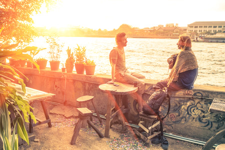 best travel destinations: Couple of best friends travelers talking at sunset - Travel concept around the world with exclusive destinations Stock Photo