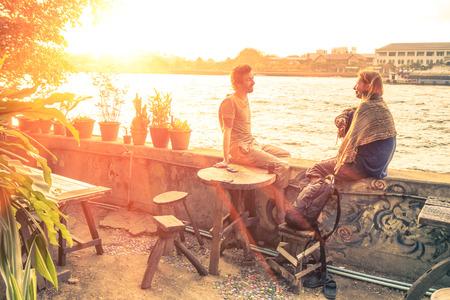 personas platicando: Un par de mejores amigos viajeros hablan en la puesta del sol - Concepto de viaje alrededor del mundo con destinos exclusivos Foto de archivo