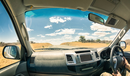 car front: Travel landscape from a car cockpit - Concept of adventure trip on the road to exlcusive destinations - Fisheye view on desert street and cloudscape during world tour in Namibia african excursion