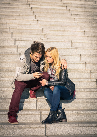 Hipster couple in love having fun with smartphone - Modern concept of connection in a relationship together with mobile phone technology - City urban lifestyle representing everyday life rapport