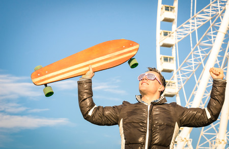 Young hipster man with longboard skate board at luna park - Concept of modern vintage alternative lifestyle with handsome guy at ferris wheel - Spring youth alternative fashion in a sunny happy day Stock Photo