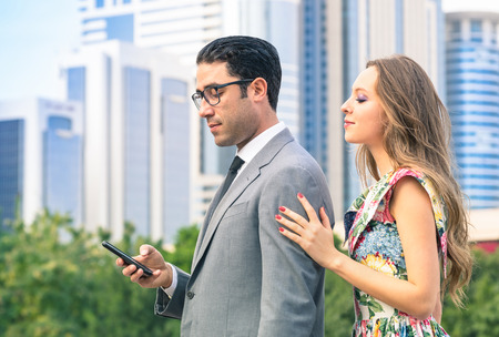 Young hipster couple in moment of mutual disinterest - Concept of breaking up connected to the alienation from new trends and technologies - Ignored girlfriend trying to keep attention from boyfriend Stock Photo