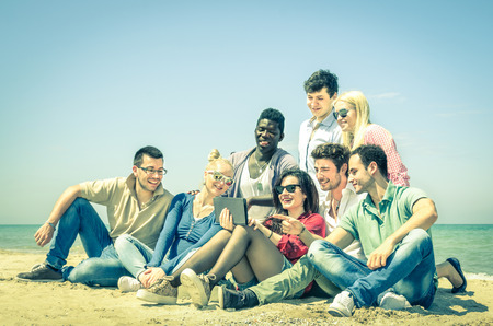 multi cultural: Group of young hipster best friends with digital tablet sitting at the beach - Concept of multi cultural friendship against racism - Interaction with new trends and technologies devices in open spaces