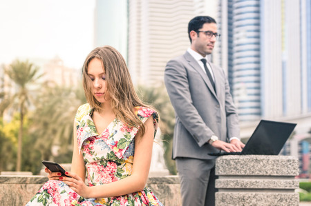 Young hipster couple in a phase of mutual disinterest and sadness - Concept of breaking up connected to the alienation from new technologies - Business man ignoring his girlfriend for working excess photo