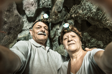 Senior happy couple taking a selfie at the entrance of Tham Phu Kham in Vang Vieng - Adventure travel in Laos and asian destinations - Concept of active elderly around the world with new technologies