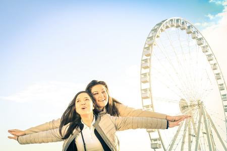 amicizia: Migliori amiche tempo godendo insieme all'aperto a luna park - concetto di amicizia e di felicit� con due amiche che hanno divertimento - Gente felice al Ferris
