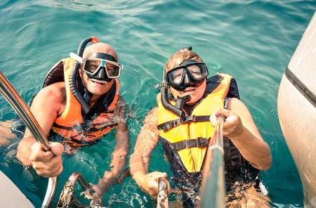 elderly adults: Senior happy couple using selfie stick in tropical sea excursion - Boat trip snorkeling in exotic scenarios - Concept of active elderly and fun around the world - Soft vintage filtered look Stock Photo
