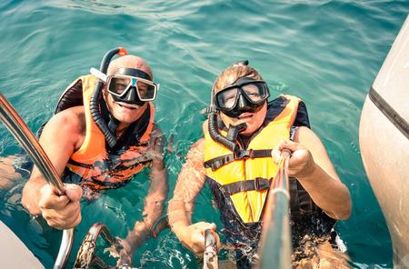 personas tomando agua: Senior stick feliz pareja usando Autofoto en excursi�n mar tropical - Barco viaje de buceo en escenarios ex�ticos - Concepto de ancianos activos y divertido en todo el mundo - vendimia Soft filtrada vistazo