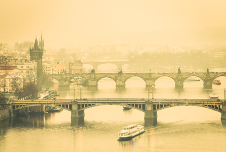 look after: View of Charles Bridge in Prague and Vltava river from Letna Hill - Warm desaturated filtered look after misty sunset with emotional filter - European capital of bohemian Czech Republic Stock Photo